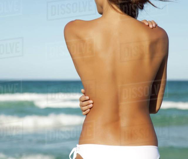 Semi Naked Woman In Bikini Bottom Hugging Self By Ocean Rear View
