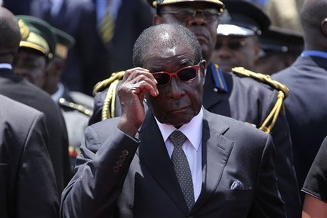 Zimbabwean President Robert Mugabe, attends the burial of Deputy President John Nkomo, at the Heroes Acre, in Harare, Zimbabwe, Monday, Jan, 21, 2013. Nkomo died of cancer aged 79. Mugabe who addressed mourners at the funeral called on Zimbabweans to be united and for peace to prevail in the country ahead of elections set for sometime this year.