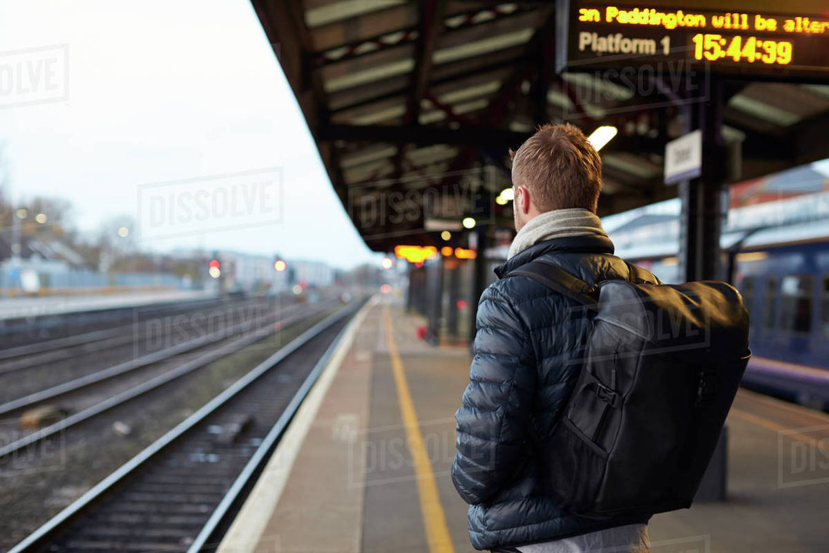 Man Standing On Railway Platform Waiting For Train To