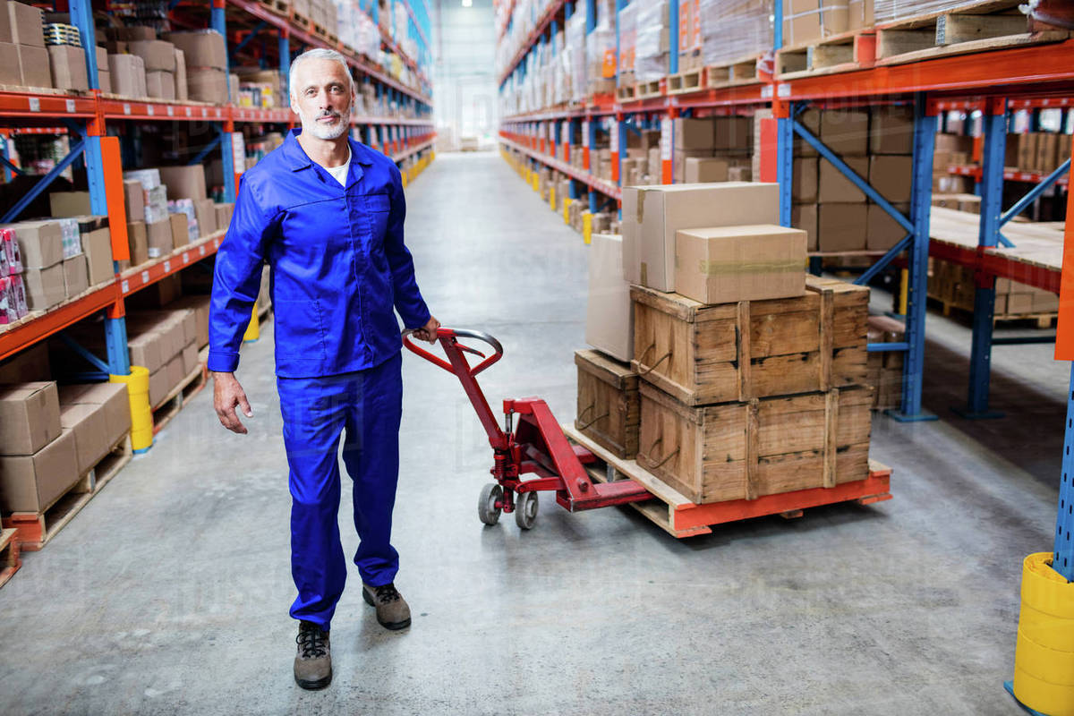 Portrait Of Man Worker Pulling The Pallet Truck In A