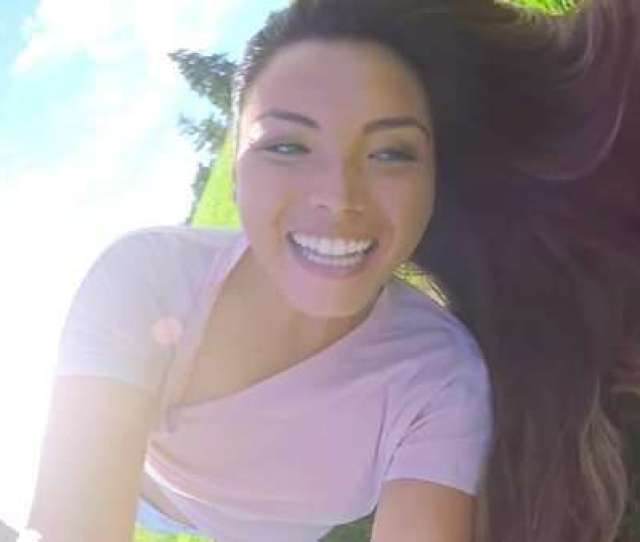 Beautiful Asian Teen Holds A Gopro And Rolls Down A Huge Grassy Hill In A Park