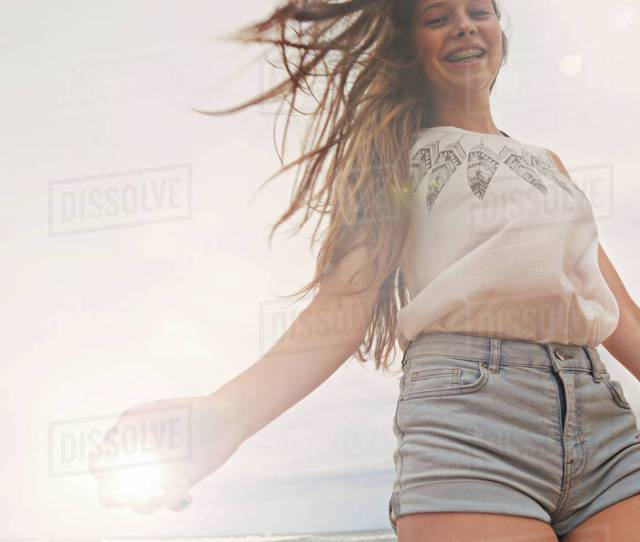 Portrait Of Teenage Girl At Beach Smiling Low Angle View