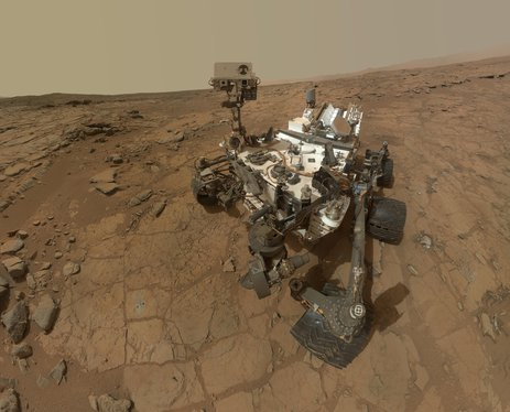 """This self-portrait of NASA's Mars rover Curiosity combines dozens of exposures taken by the rover's Mars Hand Lens Imager on Feb. 3, 2013 plus three exposures taken May 10, 2013 to show two holes (in lower left quadrant) where Curiosity used its drill on the rock target """"John Klein""""."""