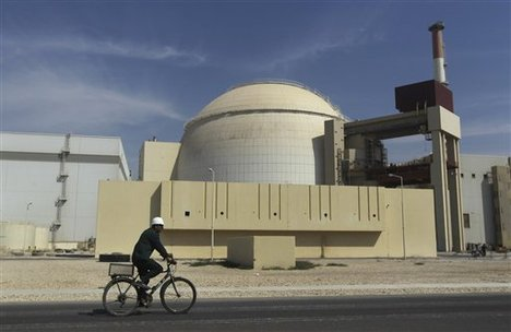 A worker rides a bike in front of the reactor building of the Bushehr nuclear power plant, just outside the southern city of Bushehr, Iran, Tuesday, Oct. 26, 2010.
