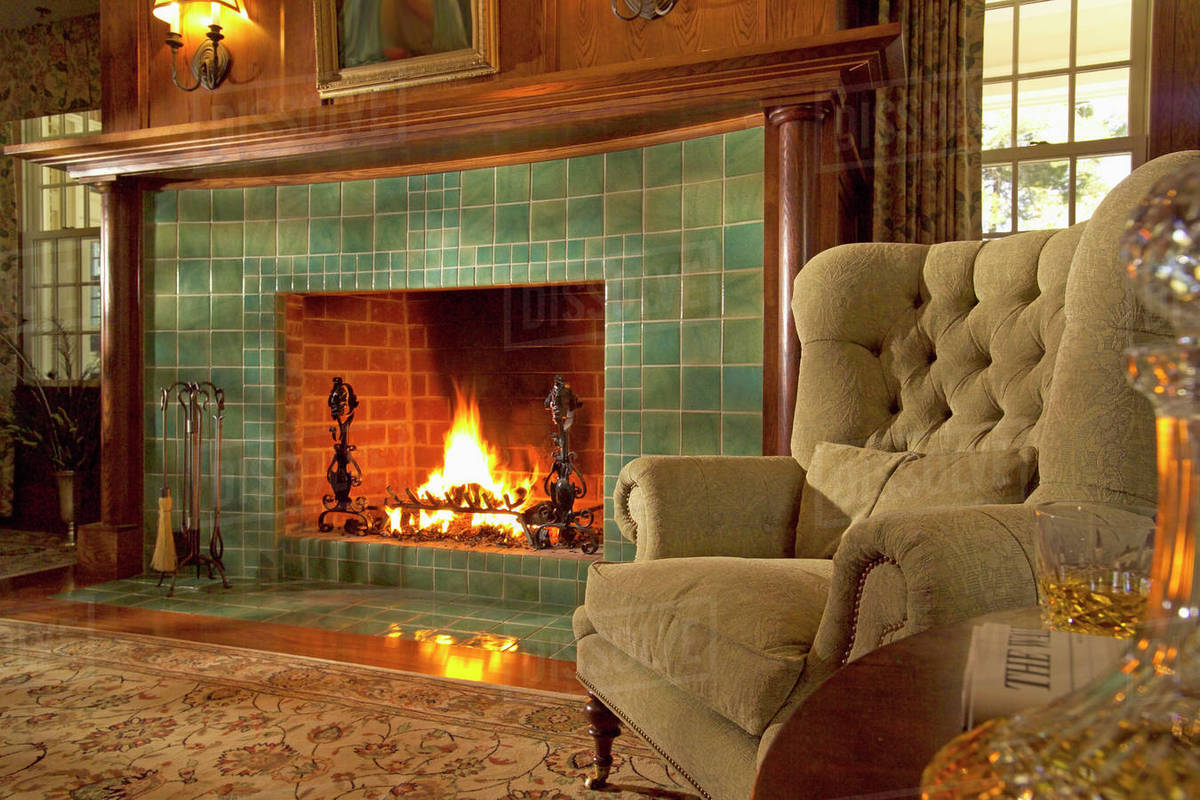 comfy armchair next to green tile fireplace with fire d145 200 272