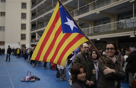People queue with the Estelada flag (pro-independence Catalan flag) to cast their vote at a polling station for an informal poll for the independence of Catalonia in Barcelona, Spain, Sunday, Nov. 9, 2014.