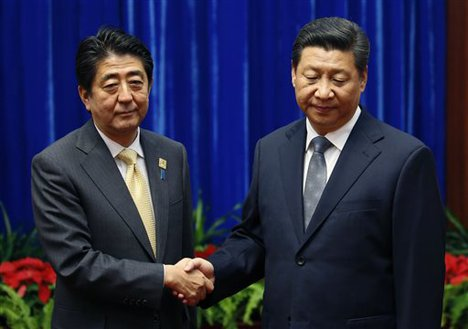 China's President Xi Jinping, right, shakes hands with Japan's Prime Minister Shinzo Abe, during their meeting at the Great Hall of the People, on the sidelines of the Asia Pacific Economic Cooperation (APEC) meetings, in Beijing, Monday, Nov. 10, 2014.