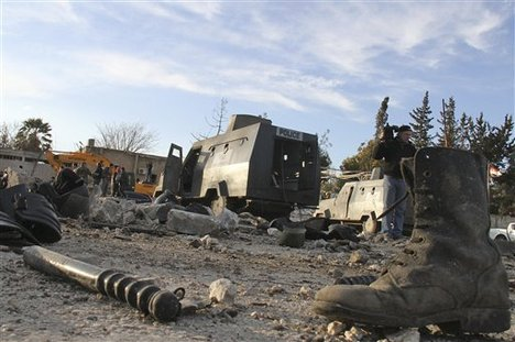 In this photo taken on a government-organized tour for the media, destroyed Syrian armored vehicles and police riots gear is seen inside a damaged Syrian police headquarters compound which was attacked by an explosion, in the northern city of Aleppo, Syria, on Friday Feb. 10, 2012.