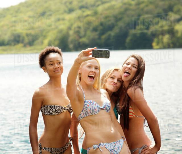 Teen Girls 16 17 With Young Woman Taking Selfie In Front Of Lake