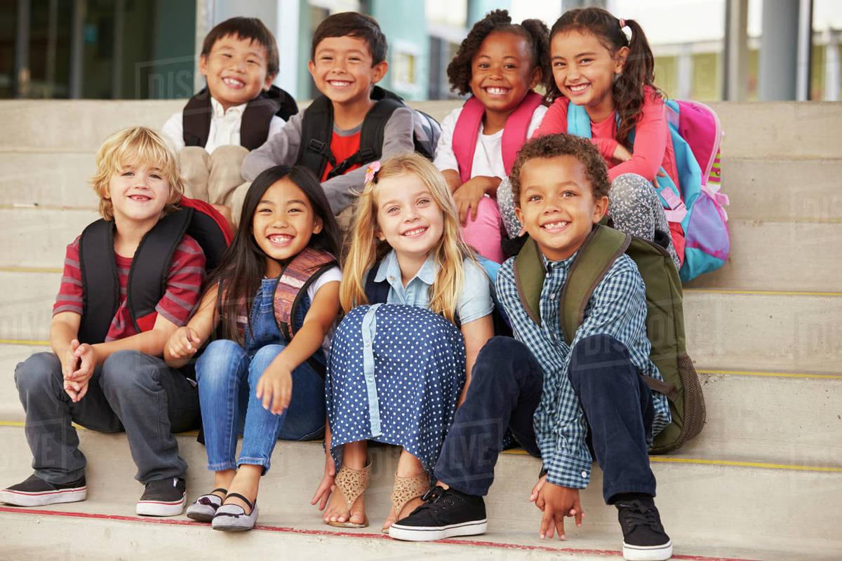 A Group Of Elementary School Kids Sitting On School Steps