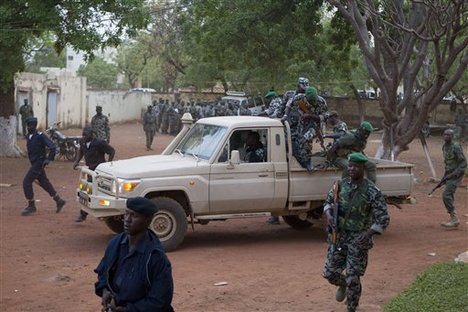 In this March 27, 2012 file photo, soldiers disembark from a truck to secure the location as coup leader Capt. Amadou Haya Sanogo, unseen, arrives at his headquarters at Kati military base, just outside Bamako.