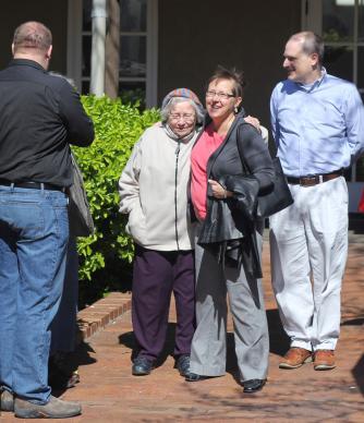 """El Rev. Cynthia Meyer (segundo desde la derecha) recibe un abrazo y buenos deseos de los seguidores después de una reunión con el Obispo metodista unido a Scott Jones 28 de marzo en Wichita, Kansas. Meyer se enfrenta a cargos disciplinarios de la iglesia después de que ella anunció que estaba en una """"relación de compromiso"""" con otra mujer."""