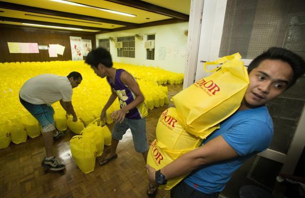 Photo par Mike DuBose, UMNS Vincent Salazar (à droite) aide une équipe de l'Agence humanitaire de l'Eglise, UMCOR, à charger des sacs pour porter secours aux survivants du Typhon Haiyan aux Philippines.