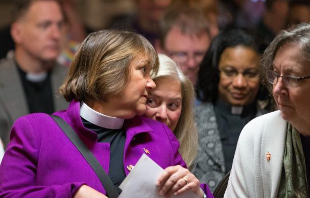 Obispo Karen Oliveto (izquierda) se inclina para hablar con su esposa, Robin Ridenour (detrás de Oliveto) antes de una reunión del Consejo de la Judicatura Metodista Unida en Newark, Nueva Jersey el máximo tribunal de La denominación falló el 28 de abril que la consagración de un obispo homosexual viola ley de la iglesia.  A la derecha está el obispo Elaine Stanovsky.  Foto de Mike DuBose, UMNS