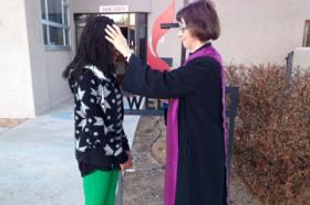 The Rev. Kim Kinsey applies ashes outside of her church building.