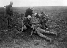Battle of Vimy Ridge. Canadian soldiers tend to a fallen German on the battlefield. (1917).