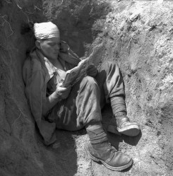 Canadian soldiers reads a comic book while laying down in a trench during the Korean War