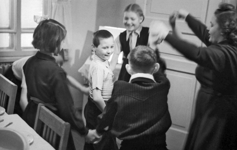 Niños felicitan a su compañero de clase en su fiesta de cumpleaños.