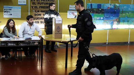 Un policía argentino camina con un perro que olfatea una posible bomba en una mesa de votación durante las elecciones primarias de mediano plazo en Buenos Aires, Argentina 13 de agosto de 2017