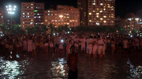 La gente mira los fuegos artificiales estallar en la playa de Copacabana, en Río de Janeiro en Año Nuevo.