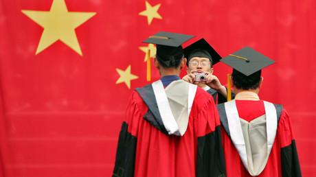 Ein Student fotografiert seine Freunde vor der chinesischen Flagge während einer Abschlussfeier an der Fudan-Universität in Shanghai am 28. Juni 2006.