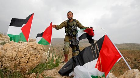 Ein israelischer Soldat entfernt palästinensische Fahnen im von Israel besetzten Westjordanland, die aus Protest gegen Trumps