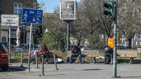 Drei Obdachlose sitzen am 23. März mit großem Abstand auf Parkbänken auf einem Platz in Berlin-Kreuzberg. Während der Corona-Krise haben Obdachlose als Risikogruppen mit massiven Einschränkungen ihrer Grundversorgung und medizinischer Hilfe zu kämpfen.