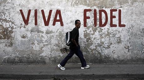 A man walks past a graffitti that reads