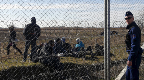 FILE PHOTO Migrants rest as a policeman watches them near Hungary's border fence on the Serbian side of the border near Morahalom, Hungary © Laszlo Balogh