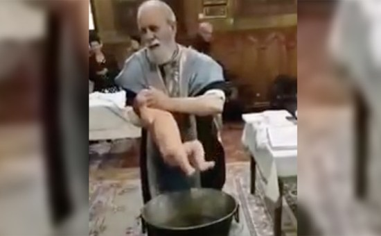 Romanian Priest Roughly Handles Baby In Baptism - Image Copyright RT.Com