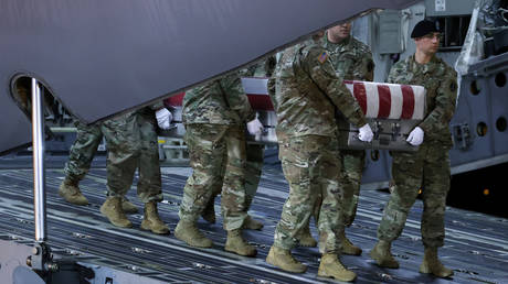 An honor guard carries the transfer case holding the remains of US Army soldiers killed in eastern Afghanistan, Dover Air Force Base, Delaware, February 10, 2020.