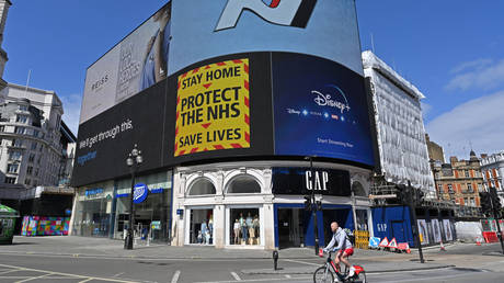 """A government sign """"Stay Home, Protect the NHS, Save Lives"""" is displayed on the advertising boards in Piccadilly Circus in London on April 13, 2020 © AFP / Glyn Kirk"""