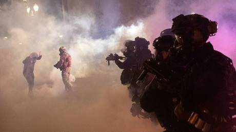 Federal law enforcement officers fire tear gas and other munitions to disperse protesters during a demonstration against police violence and racial inequality in Portland, Oregon, July 30, 2020.