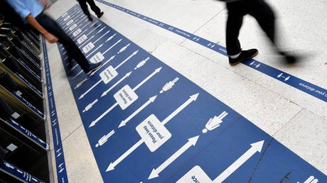 People pass social distancing markers at Waterloo station in London, Britain, September 7, 2020.