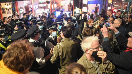 FILE PHOTO: Police officers move crowds in Soho on November 4, 2020 in London, England. Non-essential businesses, including pubs and restaurants, will be forced to close from Thursday, Nov 5, following a new national lockdown in England.