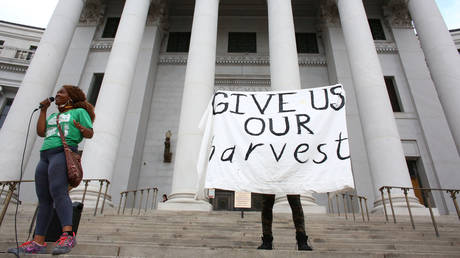 DonQuenick demands reparations and a protester raises a sign reading ?Give us our harvest in Denver, Colorado