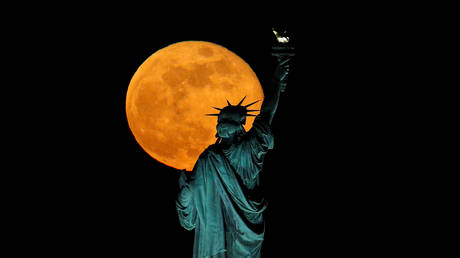 So close, yet so far away: The moon rises above the Statue of Liberty, as seen from Jersey City, May 7, 2020.