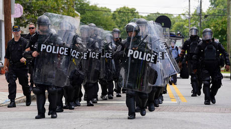 FILE PHOTO: Police officers clad in riot gear prepare to face down opposing protesters at a Confederate memorial at Stone Mountain, Georgia.