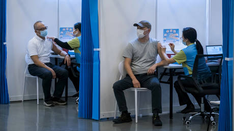 FILE PHOTO: People receive a dose of the Sinovac Biotech's COVID-19 vaccine at a community vaccination center in Hong Kong, China, February 23, 2021.