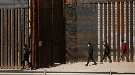 Migrants walk to a gate in the border wall after crossing the Rio Bravo river to turn themselves in to US Border Patrol agents in El Paso, Texas, March 14, 2021 © Reuters / Jose Luis Gonzalez