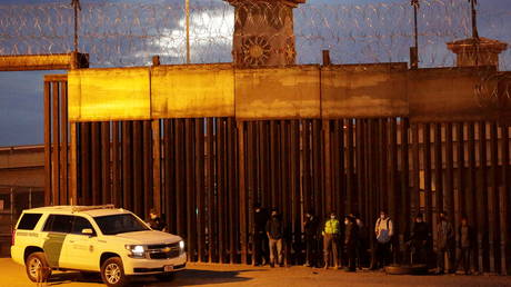 FILE PHOTO: Migrants are detained by a US Border Patrol agent as they turn themselves in to request asylum, after crossing into El Paso, Texas, as seen from Ciudad Juarez, Mexico February 2, 2021.