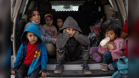 Child migrants take shelter from the rain in the back of a US Border Patrol vehicle on Sunday after crossing the border into Texas.