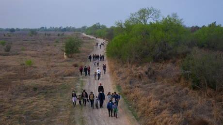FILE PHOTO: Migrants walk towards the US-Mexican border wall, March 2021. © Adrees Latif / Reuters