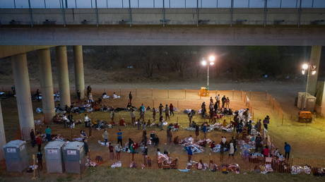 FILE PHOTO: Migrant families and unaccompanied minors take refuge in a makeshift US Customs and Border Protection processing center under the Anzalduas International Bridge after crossing the Rio Grande river into the US from Mexico, March 12, 2021