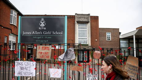 A person walks past placards attached to the fence outside the James Allen's Girls' School in south London, Britain, (FILE PHOTO) © REUTERS/Henry Nicholls