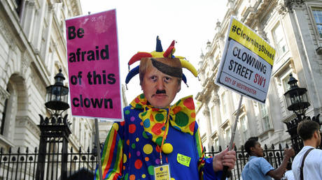 FILE PHOTO: An anti-Brexit protester wearing a clown costume and a defaced mask depicting British Prime Minister Boris Johnson holds placards in Westminster in London, UK,  August 29, 2019 © Reuters / Toby Melville