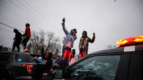 Demonstrators stand on a police vehicle during a protest after police allegedly shot and killed a man, who local media report is identified by the victim's mother as Daunte Wright, in Brooklyn Center, Minnesota, U.S., April 11, 2021.  © REUTERS/Nick Pfosi