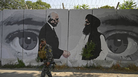 A security personnel walks past a wall mural with images of US Special Representative for Afghanistan Reconciliation Zalmay Khalilzad (L) and Taliban co-founder Mullah Abdul Ghani Baradar, in Kabul on July 31, 2020.