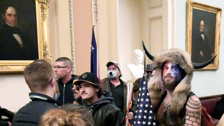 FILE PHOTO: Jacob Chansley, also known as the 'QAnon Shaman,' stands with other supporters of then-President Donald Trump as they demonstrate on the second floor of the US Capitol, January 6, 2021.