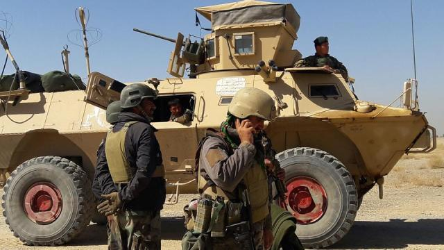 (FILES) In this file photo taken on May 05, 2021 Afghan security forces stand near an armoured vehicle during ongoing fighting between Afghan security forces and Taliban fighters in the Busharan area on the outskirts of Lashkar Gah, the capital city of Helmand province.